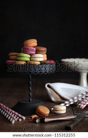 Delicious macaroons on cake stand with dark background - stock photo