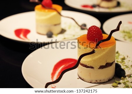 Delicious Mango Mousse Cake topped with strawberries and chocolate - stock photo