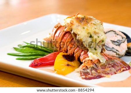 Delicious meal of lobster and stuffed chicken served with sweet peas, potatoes, peppers and oysters. - stock photo