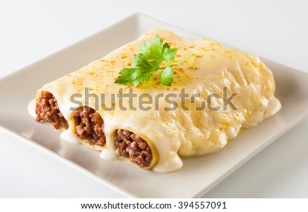 Delicious meat filled pasta on a plate. Italian cannelloni, Spanish canelones. - stock photo