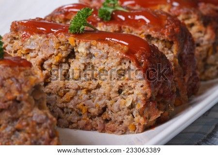 Delicious meat loaf with ketchup on a white plate, macro horizontal  - stock photo