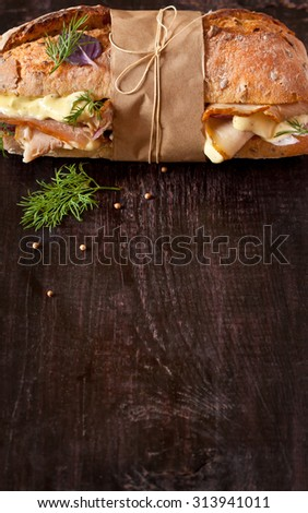 Delicious meat sandwich wrapped in paper with kitchen twine on wood background with copy space for text. - stock photo