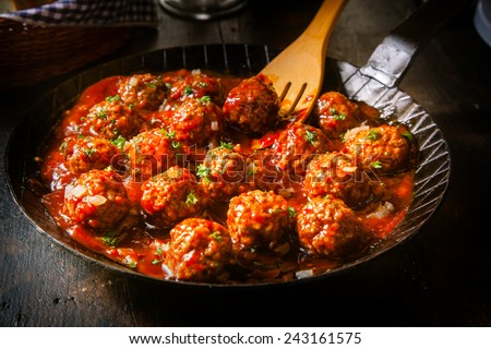 Delicious meatballs made from ground beef in a spicy tomato sauce served in a skillet or old metal pan in a restaurant - stock photo