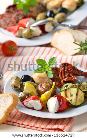 Delicious mediterranean antipasti (stuffed peppers, stuffed mushrooms, grilled zucchini, stuffed green olives, black olives, fried and pickled champignons, sun-dried tomatoes) - stock photo