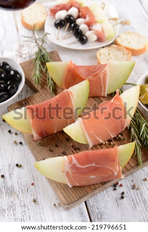 Delicious melon with prosciutto on table close-up