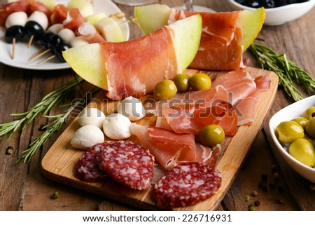 Delicious melon with prosciutto on table close-up - stock photo