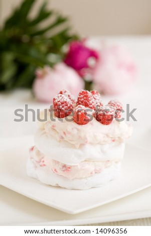 Delicious meringue dessert with raspberry cream and fresh raspberries - stock photo