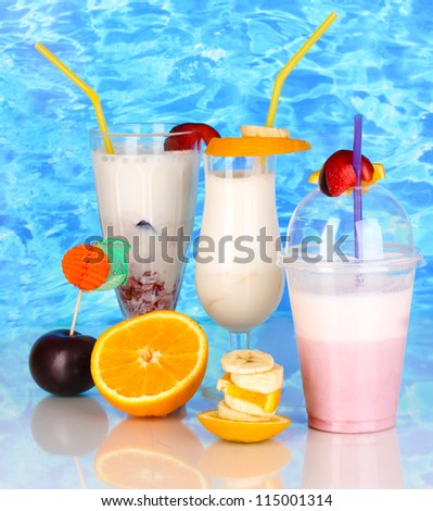 Delicious milk shakes with fruit on blue sea background