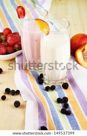 Delicious milk shakes with strawberries and peach on wooden table close-up