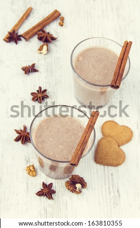Delicious Milkshake with Cookies and Spices on White Wooden Background. Winter - stock photo