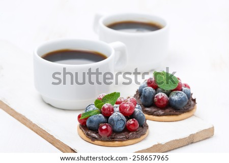 delicious mini cakes with chocolate cream and berries and a cup of coffee, close-up - stock photo