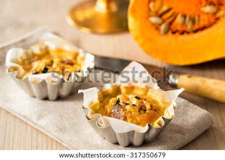 Delicious mini quiche with vegetables and pumpkin on a wooden table. - stock photo