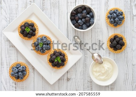 Delicious mini tart with fresh blackberries and blueberries on wooden background - stock photo