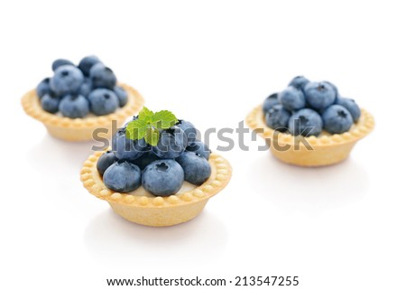Delicious mini tart with fresh blueberries isolated on white - stock photo