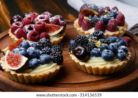 Delicious mini tarts with fresh berries and custard on wooden cutting board - stock photo