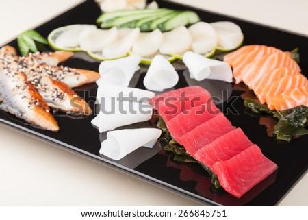 delicious mixed sashimi on a black plate - stock photo
