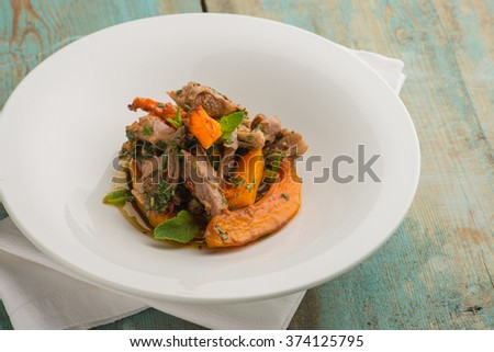 Delicious modern meat stew with vegetables on wooden table - stock photo