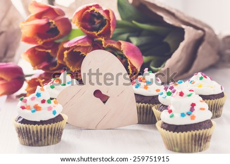 Delicious Mothers day  chocolate cupcakes  with spring tulips and wooden heart shape with free text space, pastel retro tones - stock photo