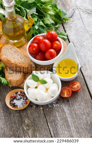 delicious mozzarella and ingredients for the salad on a wooden background, vertical, top view, close-up - stock photo