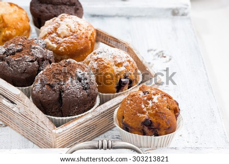 delicious muffins on a wooden tray on white background, horizontal