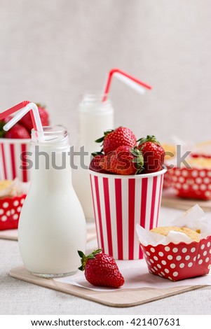 Delicious muffins, strawberries and milk in bottles. Selective focus. - stock photo
