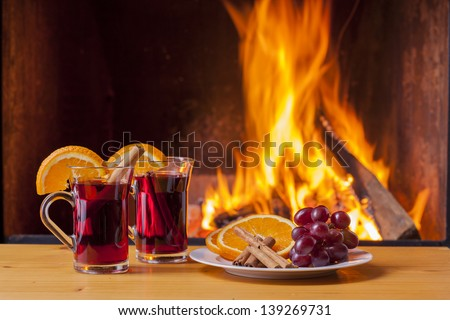 delicious mulled wine with ingredients at romantic fireplace - stock photo