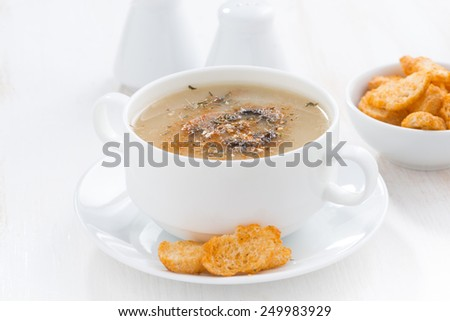 delicious mushroom cream soup with croutons on white table, close-up - stock photo