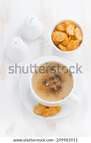 delicious mushroom cream soup with croutons on white table, top view, vertical - stock photo