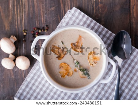 Delicious mushroom soup in a white bowl on the wooden table, top view - stock photo