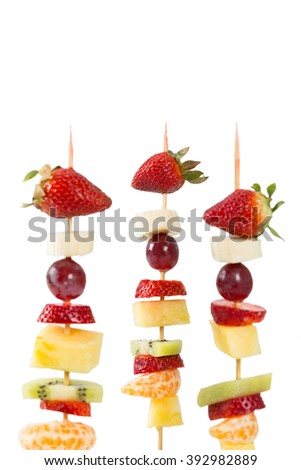 Delicious natural fruit skewers with white background - stock photo