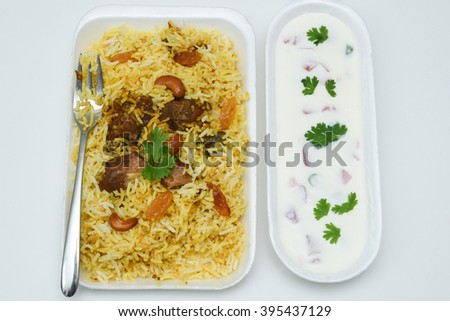 Delicious North Indian food Hydrabadi chicken biriyani, vegetable Biriyani, Chicken pulao with yogurt onion starter. Fresh Vegetable salads. basmati rice, herbs, raitha. Ramadan Kareem,  Eid-Ul-Adha - stock photo