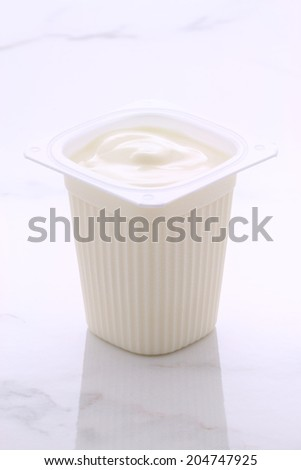 Delicious, nutritious and healthy fresh plain greek yogurt. On vintage Italian carrara marble retro styling. - stock photo