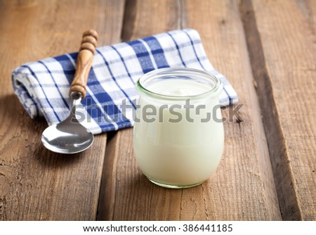 Delicious, nutritious and healthy yogurt in a glass jars with spoon on wooden background