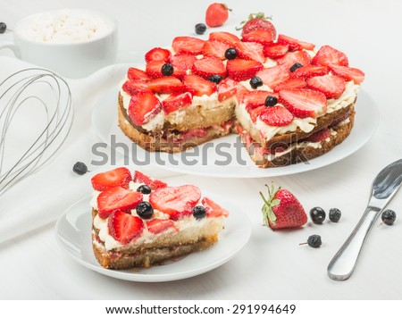 Delicious nutritious cake with fresh strawberries decorated with chokeberry, white cup with whipped cream,  whisk, strawberry, napkin, plate,  good morning - stock photo