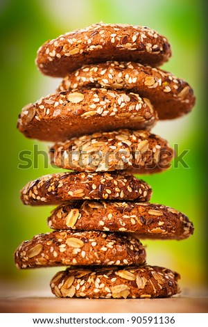 delicious oatmeal cookies with splash of sunflower seeds, sesame seeds on wooden table laid out in row on green background - stock photo