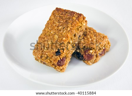 Delicious oaty cherry and raisin flapjacks stacked together on a plate, on a background of a white tablecloth.