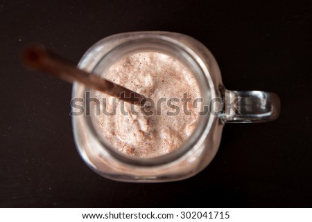 Delicious of chocolate frappe with straw in glass cup on black wood table. Top view. - stock photo