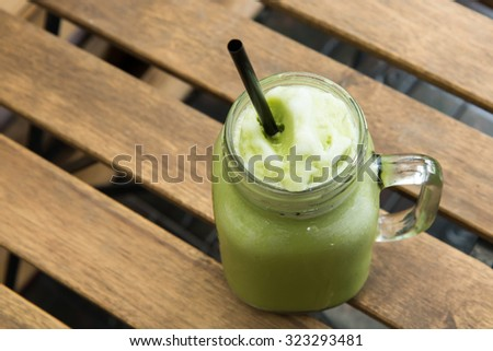 Delicious of green tea frappe with tube in glass cup on wood table. homemade. - stock photo