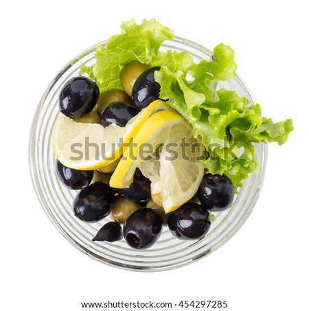 Delicious olives with lemons and lettuce in a glass bowl. Isolated on a white background.