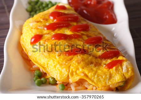 Delicious Omurice omelette with rice, green peas and ketchup close-up on a plate. horizontal - stock photo