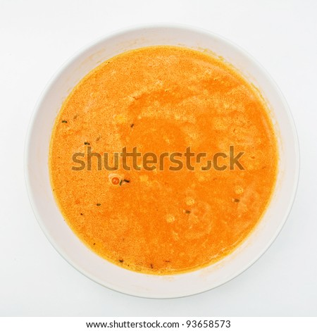 Delicious orange pumpkin soup in a deep white plate, top view - stock photo
