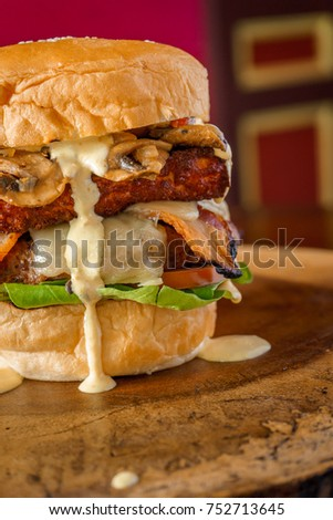 Delicious organic burger with mushrooms accompanied by fried cheese, lettuce, bacon, avocado and garlic sauce with spices, on a colorful background on a wooden table.