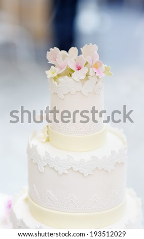 Delicious original white wedding cake decorated with flowers - stock photo