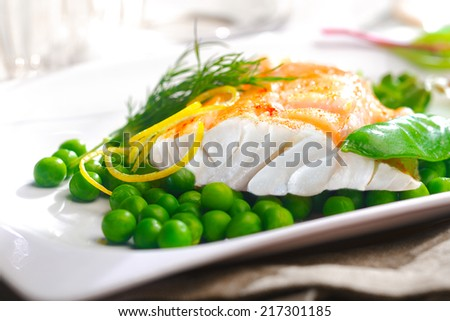 Delicious oven baked fish or grilled fillet or steak with peas, a mangetout pod, lemon zest and fresh dill for a nutritious seafood dinner - stock photo