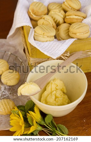 Delicious oven fresh baked melting moments shortbread biscuits with sweet filling and daisies in a rustic setting. - stock photo