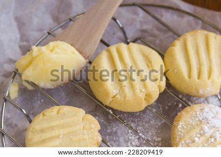 Delicious oven fresh baked melting moments shortbread biscuits with sweet filling on a spoon.