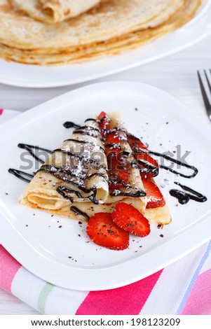 Delicious pancake with strawberries and chocolate on plate on table - stock photo