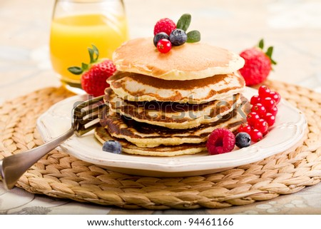 delicious pancakes on morning breakfast table with fruits - stock photo