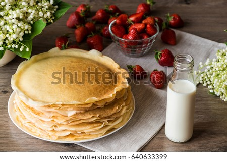 Delicious pancakes on wooden table with strawberries and milk