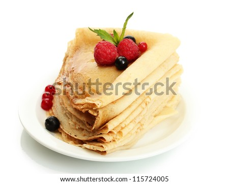 Delicious pancakes with berries and honey on plate on wooden table - stock photo